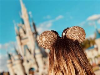 close up of the back of a little girl's head wearing mouse ears with Disney World in the background