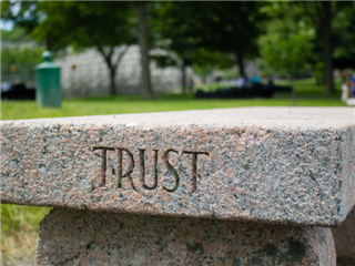 A concrete bench with the word trust etched in the side in a cematary