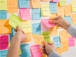 Managers using sticky notes to brainstorm their customer experience design
