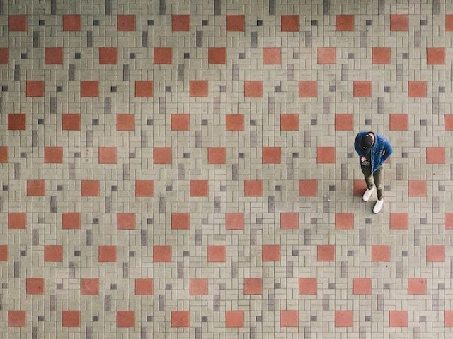 man standing on patterned tile floor, looking intently at his phone