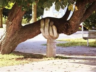 hand sculpture supporting a tree