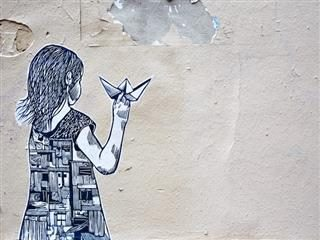 wheatpaste art on wall of girl  holding paper airplane