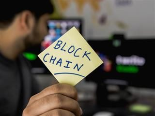 man holding up post it note with blockchain written on it