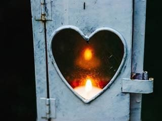 flame behind a heart cut out in a door