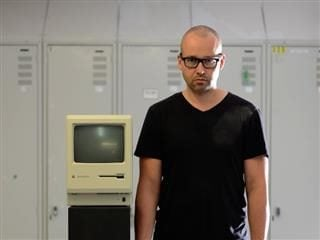 man standing next to an old Apple computer