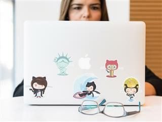 close up of laptop covered in stickers with partial shot of woman working on it