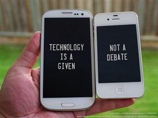 "Two iPhones in someone's hand. One of the left says, ""Technology is a given"" on the screen, the one of the right says, ""Not a debate"" on the screen"