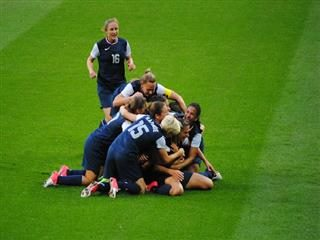 Members of the USA Women's Soccer team celebrate with hugs on the field.