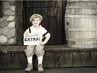 """Un petit garçon assis et tenant un journal qui dit """"supplémentaire"""" là-dessus."""