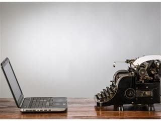 A laptop facing and antique typewriter - change management and technology concept