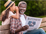Young girl whispers into a man's ear as he sits on a bench and reads the business section of a newspaper.