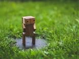 robot carved out of wood standing in the grass