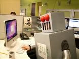 Person dressed up in a robot costume typing on a computer in a cubicle.