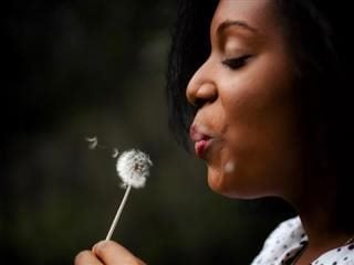 woman blowing on a dandelion to make a wish