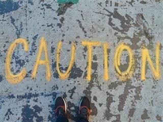"person standing in front of the word ""caution"" written on sidewalk"