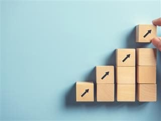 image of a woman's hand stacking blocks in stair steps with arrows pointing upward