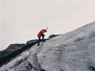 climbing a mountain with a pick axe