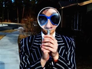 person looking out from behind a big magnifying glass