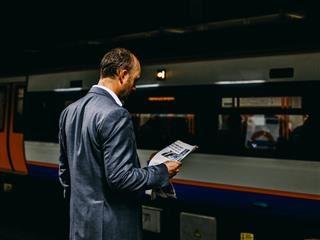 man reading a newspaper on a subway platform