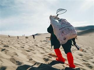 hiking uphill in sand with a heavy backpack on