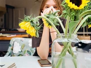 woman holding her head in her hands looking tired, jar of sunflowers  on the table in front of her