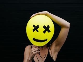 person holding a balloon in front of their face with a face drawn on it