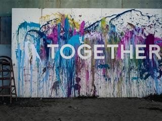 A wall with multi-colored graffiti that says Together. - Edge Computing and 5G Development Synergy Concept