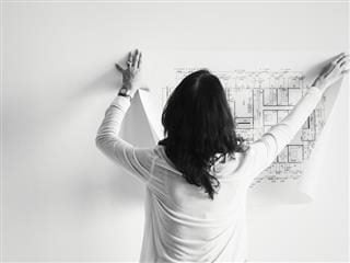 woman pinning up architect's blueprints on a wall