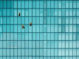 Trois nettoyeurs de vitres sur un bâtiment au toit de verre suspendu au-dessus de la rue