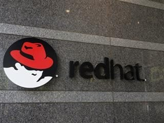 red hat linux logo on building's wall - IBM acquires red hat