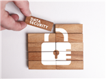 wooden blocks pushed together to create a picture of a white lock. One block says data security - workplace data security concept
