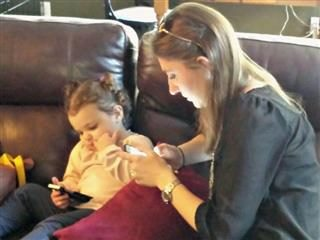 A woman and a baby simultaneously use mobile devices