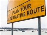 "close up of a road sign reading: ""Plan Your Alternative Route"""