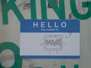 hello my name is nametag stuck on public sign. doodle of a broken screen on the nametag