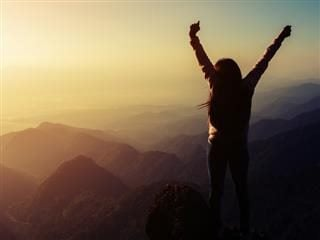 Silhouette woman rising hands on mountain in morning