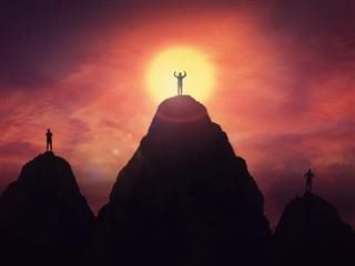 People standing on top of three adjacent mountains.