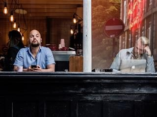 two men sitting in a cafe window on devices