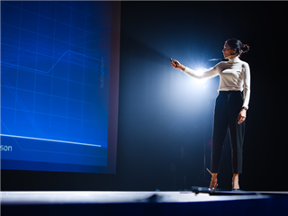 A businesswoman presenting at a conference, clicking through slides on a screen behind her
