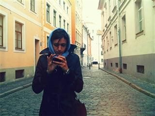 Woman in a brick street looking at her smart phone.