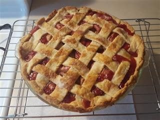strawberry rhubarb pie cooling on a rack