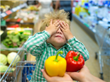 A child in a shopping cart with his hands over his eyes and someone is holding two peppers in front of him, asking him to choose - API vs SDK concept.