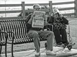 Black-and-white photo of a man reading a newspaper on a bench outside while a woman next to him in a wheelchair covers her head with paper.
