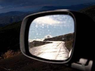 side-view mirror showing a road and a mountainous backdrop.