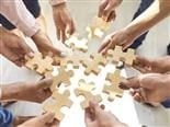 a group of hands holding puzzle pieces attempting to connect them.