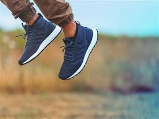 man's feet in sneakers jumping in air