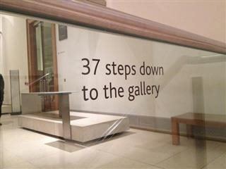 "a sign acknowledging potential challenges related to disabilities. sign reads ""37 steps down to the gallery"""
