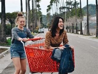 two young women playing with a shopping cart, laughing