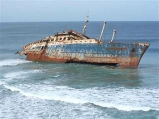 abandoned, rusted ship resting in shallow waters.