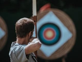 an archer facing a target with bow drawn