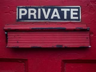 private sign over a letter opening in a red door